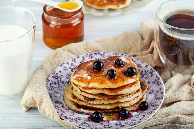 Вкусный завтрак. стопка блинов с медовым сиропом, стакан молока, кофе эспрессо и мед на деревянной белой