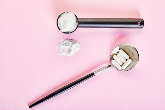 Коллагеновый порошок и таблетки по ложкам на розовой поверхности