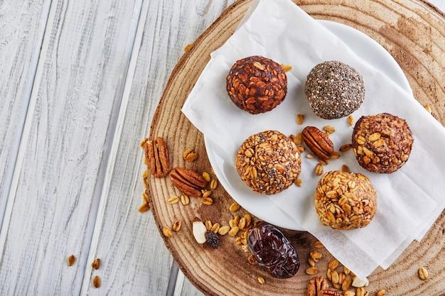 健康的な有機エネルギーボールミューズリーはナッツ、ココア、チア、ハチミツを食べた-ビーガンベジタリアンの生のスナックや食べ物。コピースペース。
