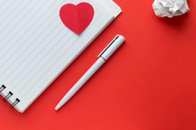 空白のメモ帳、ペン、明るい赤の背景に紙を丸めてボールに心。愛のメッセージ。バレンタインデーのテーマ。フラット横たわっていた、トップビュー、コピースペース。