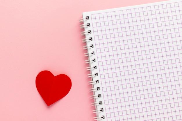ピンクの背景の空白のノートブックと赤い紙のハートを開きます。バレンタインデーとロマンチックな休日の概念。愛のメッセージ。平面図、コピースペース付きのフラットレイアウト。