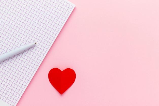 ピンクの背景の空白のノートブック、ペン、赤い紙のハートを開きます。バレンタインデーとロマンチックな休日の概念。愛のメッセージ。平面図、コピースペース付きのフラットレイアウト。