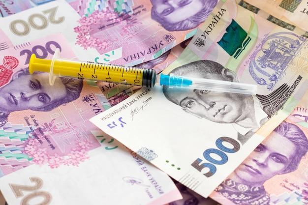 ウクライナの紙幣の山に注射器