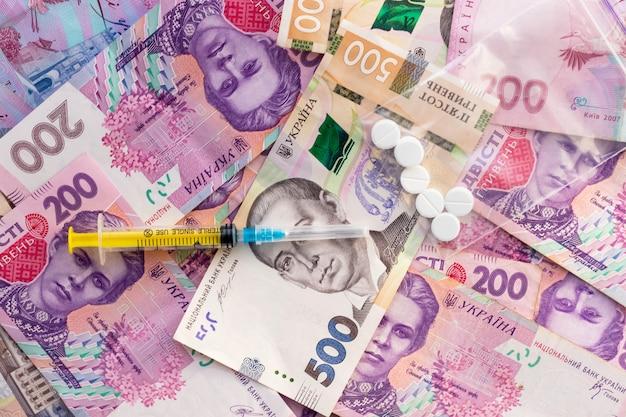 シリンジ、ジップロックビニール袋の丸薬、たくさんのウクライナのお金。薬物の販売。