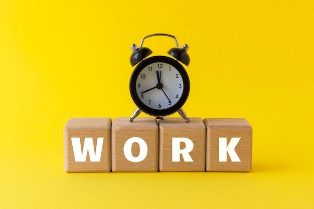 目覚まし時計とテキストのウッドブロックは明るい黄色の背景で動作します。ビジネス、キャリア、時間の無駄、先延ばしのコンセプト。