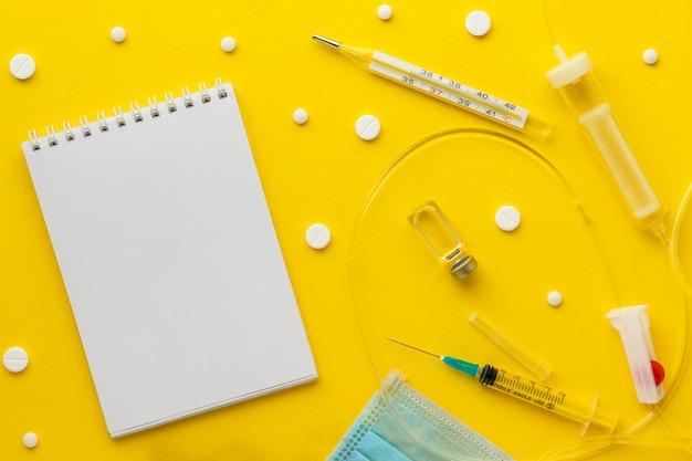 Пустой блокнот, шприц, термометр, вакцинный флакон, капельница, таблетки, медицинская маска и перчатки на желтом фоне