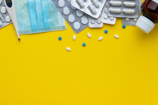 Медицинская маска, бутылка с жидкостью, электрический термометр, таблетки и капсулы на желтом фоне
