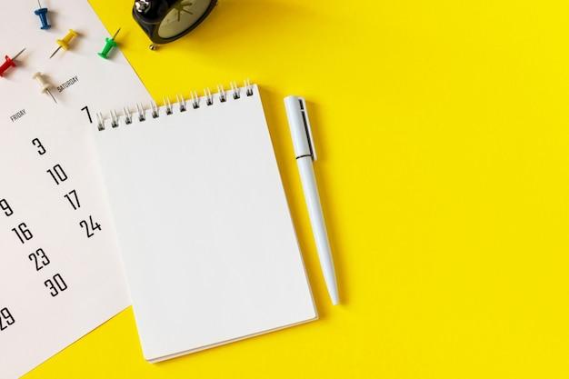 ペン、画鋲、黄色の背景に目覚まし時計で空白のノートブック
