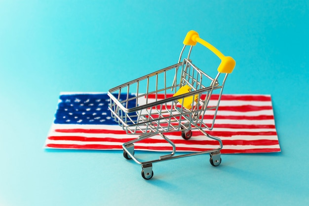 ミニスーパーショッピングカートと抽象的な手が黄色の背景にアメリカの国旗を描いた