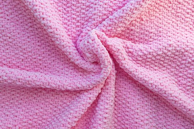 柔らかい柔らかい糸で作られた明るいピンクのニット格子縞