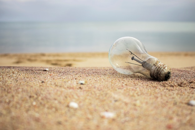 Старая лампочка на песке