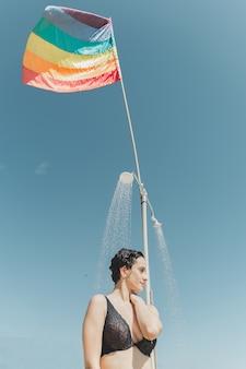 Девушка, принимающая душ на пляже под ткацким флагом лгбт