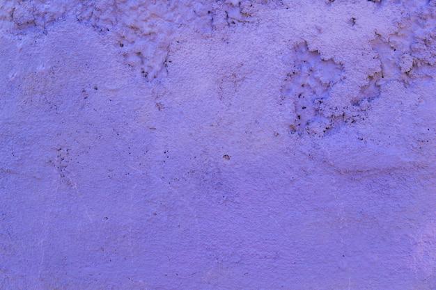 コンクリートの壁のテクスチャは紫色です。生石膏壁の背景