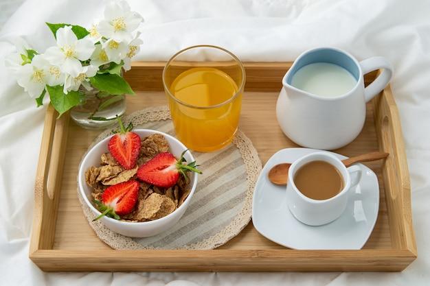 ベッドでの朝食。コーヒー、オレンジジュース、イチゴ、ミューズリーの木製トレイ。繊細な白い花を持つジュエリー。