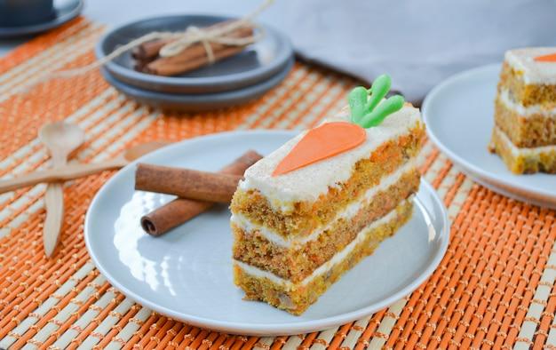 キャロットケーキの日。祝日。チョコレートニンジンで飾られたクリームチーズのフロスティングとキャロットケーキ