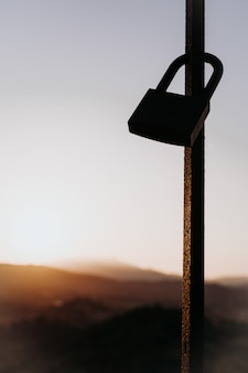 Закрытый замок на заборе в закат