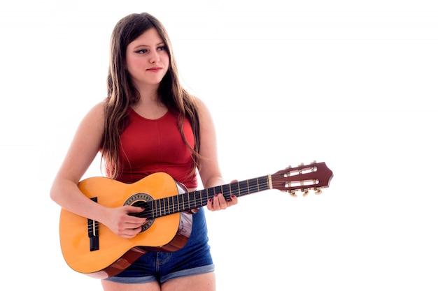 Девочка-подросток играет на испанской гитаре