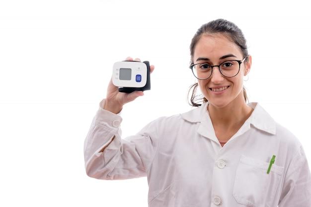Молодая медсестра в очках держит и показывает тензиометр