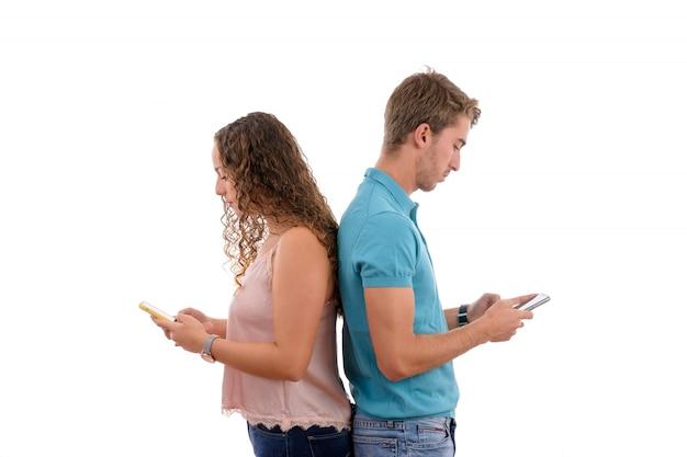 白い背景に分離された退屈の携帯電話でそれぞれ若いカップル