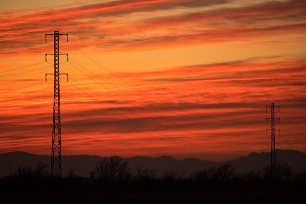 赤い夕日のバックライト付きの電気塔