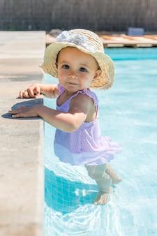 スイミングプールで帽子をかぶった女の赤ちゃんがカメラを見てください。