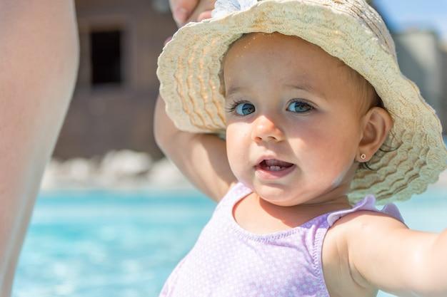 帽子の女の赤ちゃんは、スイミングプールで笑顔します。