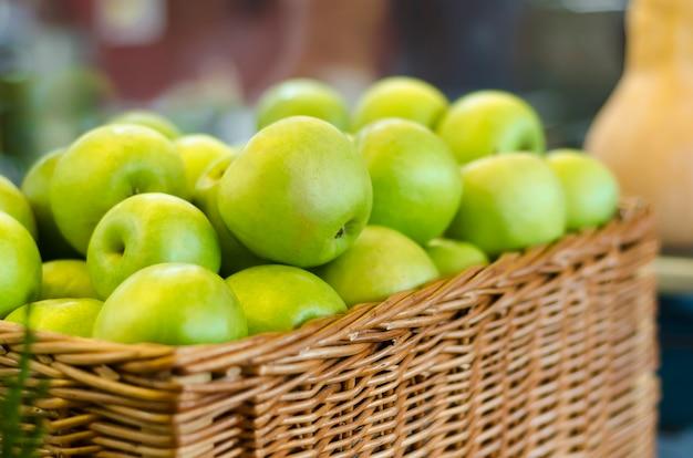 枝編み細工品バスケットで熟した青リンゴ
