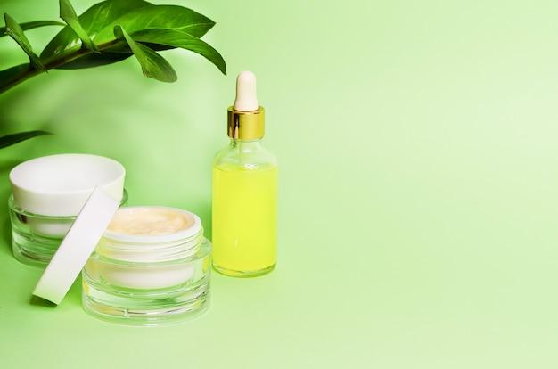Понятие красоты. натуральная косметика класса люкс, крем, маска, сыворотка с витамином с для ухода за кожей. аксессуары косметолога на зеленом фоне, копией пространства