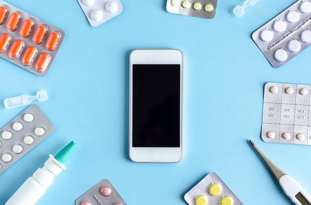 Вид сверху, плоская раскладка таблеток, лекарств, назальный спрей, термометр, жаропонижающее на синем
