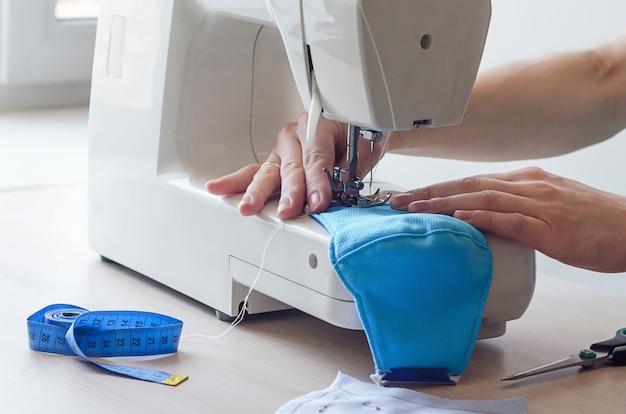検疫期間中に女性の手が医療用フェイスマスクを縫う