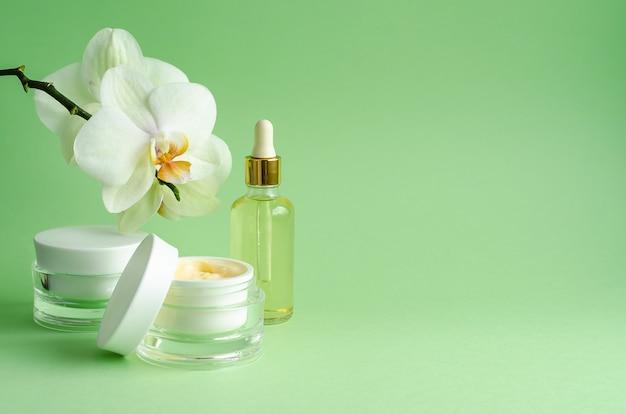ナチュラルコスメアンチエイジング、シワ改善、肌のハリ、ハリに。クリーム、マスク、血清、液体、顔のケア、緑色の背景で蘭の花の瓶の中のオイル。バナー、コピースペース