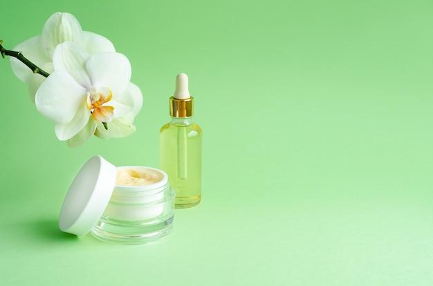 緑の背景に蘭の花と自然派化粧品。クリーム、ガラス瓶入りマスク、美容液、液体、家庭用ボトル入りオイル、プロのフェイスケア。バナー、テンプレート、コピースペース、ソフトフォーカス