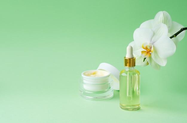 緑の背景に自然化粧品アンチエイジング、アンチリンクル、若さ、肌の弾力性。クリーム、瓶入りマスク、美容液、液体、ボトル入りオイル。顔と体のケア。バナー、テンプレート、コピースペース