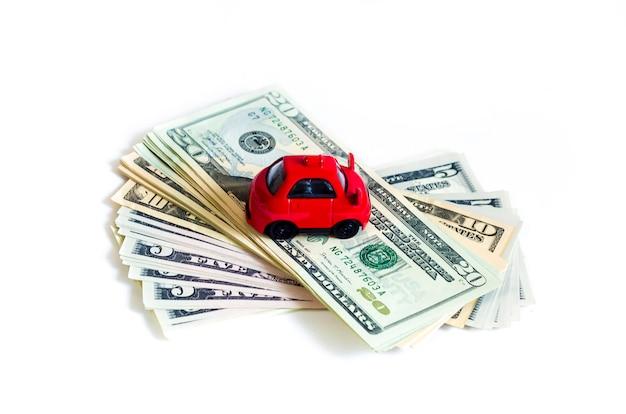 Игрушка красный автомобиль на стопку денег долларовых купюр. американские доллары купить машину в кредит. накопить на автомобиль.