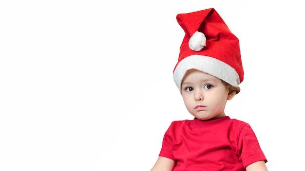 Задумчивый расстроен маленькая девочка в красном костюме и шляпу санта на новый год. ребенок ждет подарок на рождество.