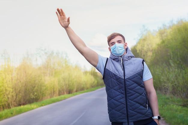 自動車、車を止めようとしているコロナウイルスの予防のための医療マスクの男。