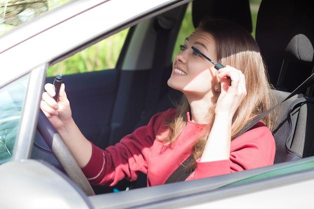 車のホイールに座っている若い幸せな女