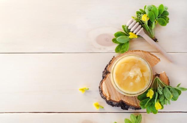 Мед из желтого цветка акации на деревянном фоне