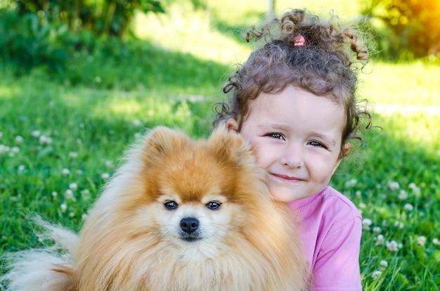 屋外で犬を抱いて幸せな少女の肖像画。美しい赤ちゃんとポメラニアンスピッツ。子供とペットが探しています