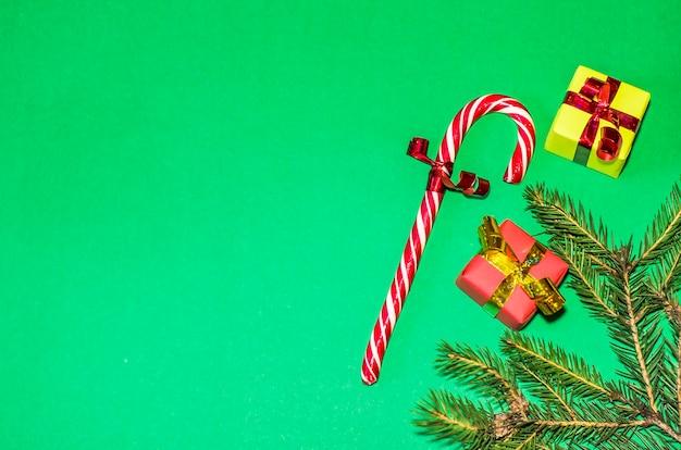 新年、休日、お祝いのコンセプト。緑の背景の贈り物。クリスマスツリーの贈り物、キャンディー杖。平干し、コピースペース