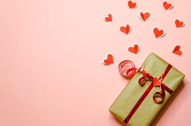 赤いリボンと新年、クリスマス、バレンタインデー、誕生日にトレンディなピンクの背景に愛の認識でそれから飛んで心のギフト。