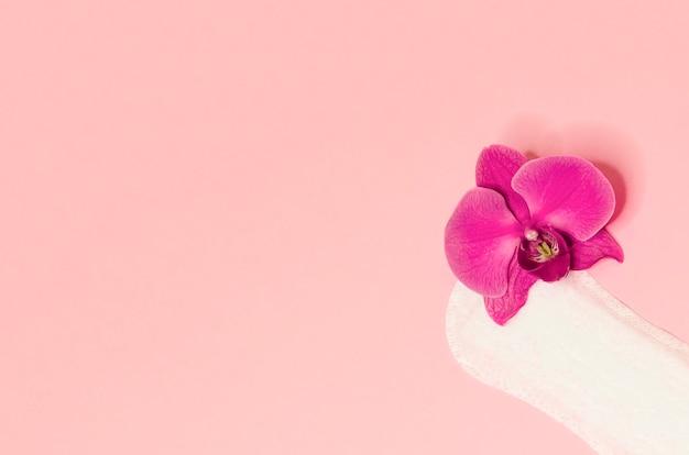 Гигиеническая прокладка с цветочной орхидеей на розовом фоне. ежедневный уход, гигиена и чистота женщины. скопируйте место для текста