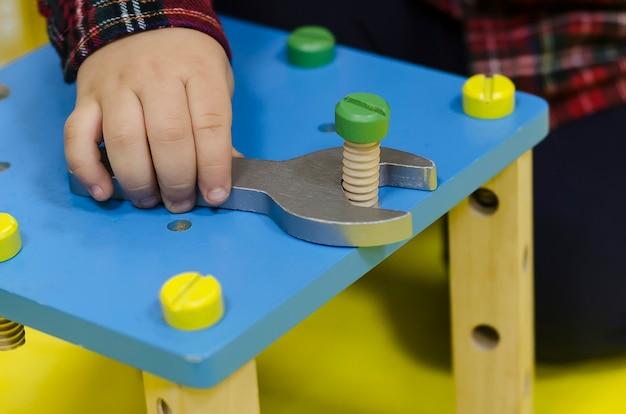 Игрушечные мужские инструменты. гаечный ключ в руках. развитие мелкой моторики у детей по системе монтессори. деревянные игрушки для детей.