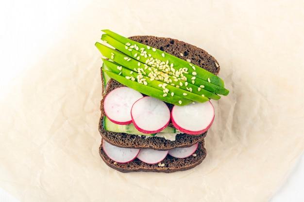 Супер-пупер открытый вегетарианский бутерброд с различными начинками: авокадо, огурец, редис на бумаге на белом фоне. здоровое питание. органическая и вегетарианская еда. закройте, скопируйте пространство для текста
