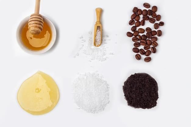 天然オーガニック素材の自家製スキンケア。クレンジングと栄養化粧品。美容製品:白い背景の上の緑の葉の間でクリーム、蜂蜜、コーヒースクラブ。クローズアップ、テキスト用のスペースをコピー