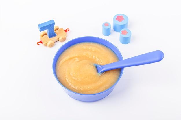 ベビーフード。新鮮な自家製アップルソース。生地にフルーツのピューレ、テーブルに子供のおもちゃが入った青いボウル。適切な栄養と健康的な食事の概念。オーガニックとベジタリアンのフードテキスト