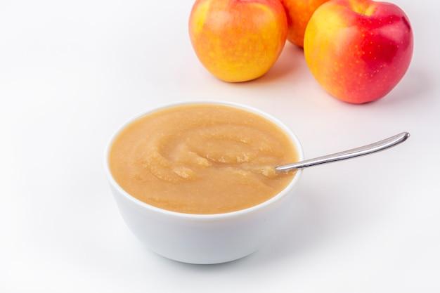 新鮮な自家製アップルソース。適切な栄養と健康的な食事の概念。オーガニックおよびベジタリアン料理。生地にフルーツピューレとテーブルの上のリンゴをカットした白いボウル。ベビーフード。コピースペース