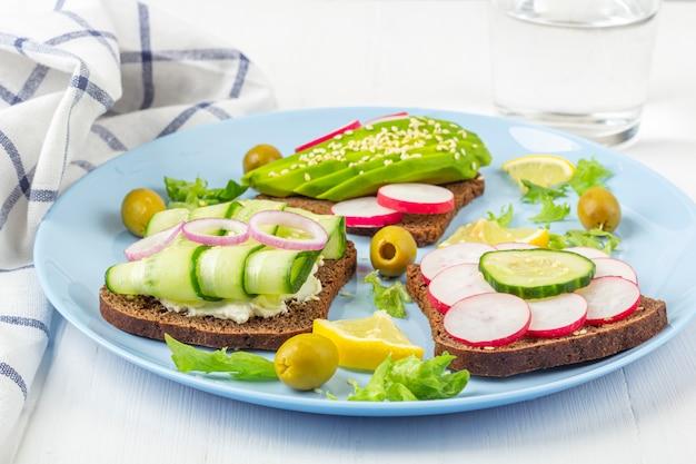 Супер-пупер открытый вегетарианский бутерброд с различными начинками: авокадо, огурец, редис на тарелку и стакан воды на белом фоне. здоровое питание. текст из органических и вегетарианских блюд