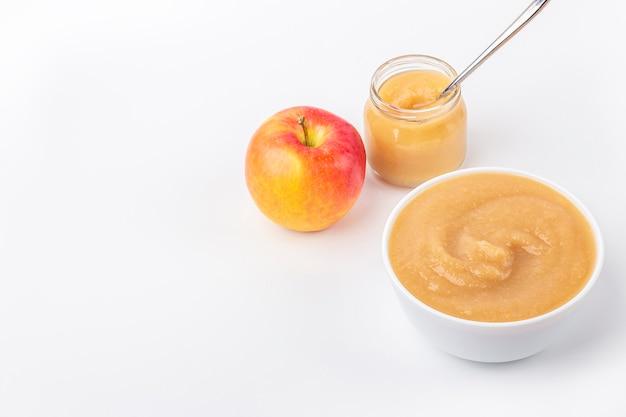 白いボウルと白いテーブルにフルーツピューレの瓶で新鮮な自家製アップルソース。適切な栄養と健康的な食事の概念。オーガニックおよびベジタリアン料理。ベビーフードのテキスト