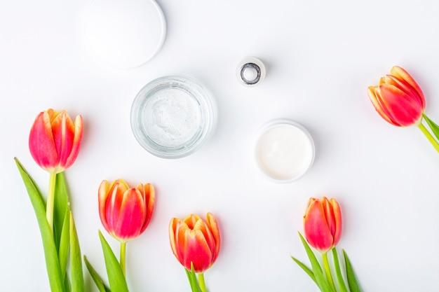 天然オーガニックの自家製化粧品コンセプト。スキンケア、治療、美容製品:白い背景の春の赤いチューリップの花の中でクリームと血清の容器。フラットレイアウト、テキスト用のコピースペース